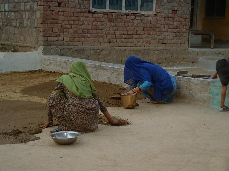 Applying Cow Dung To The Traditional Mud Floors In The Courtyard